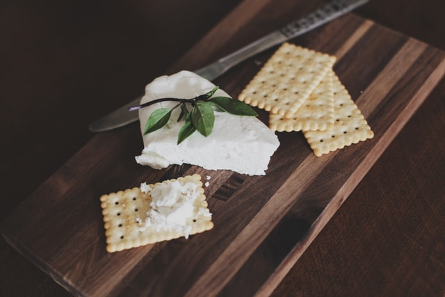 Soft white cheese on cutting board with crackers