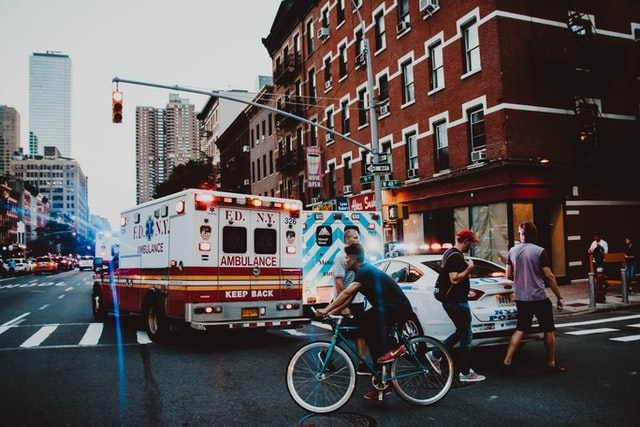 NY Ambulance and police cars at an intersection of busy street