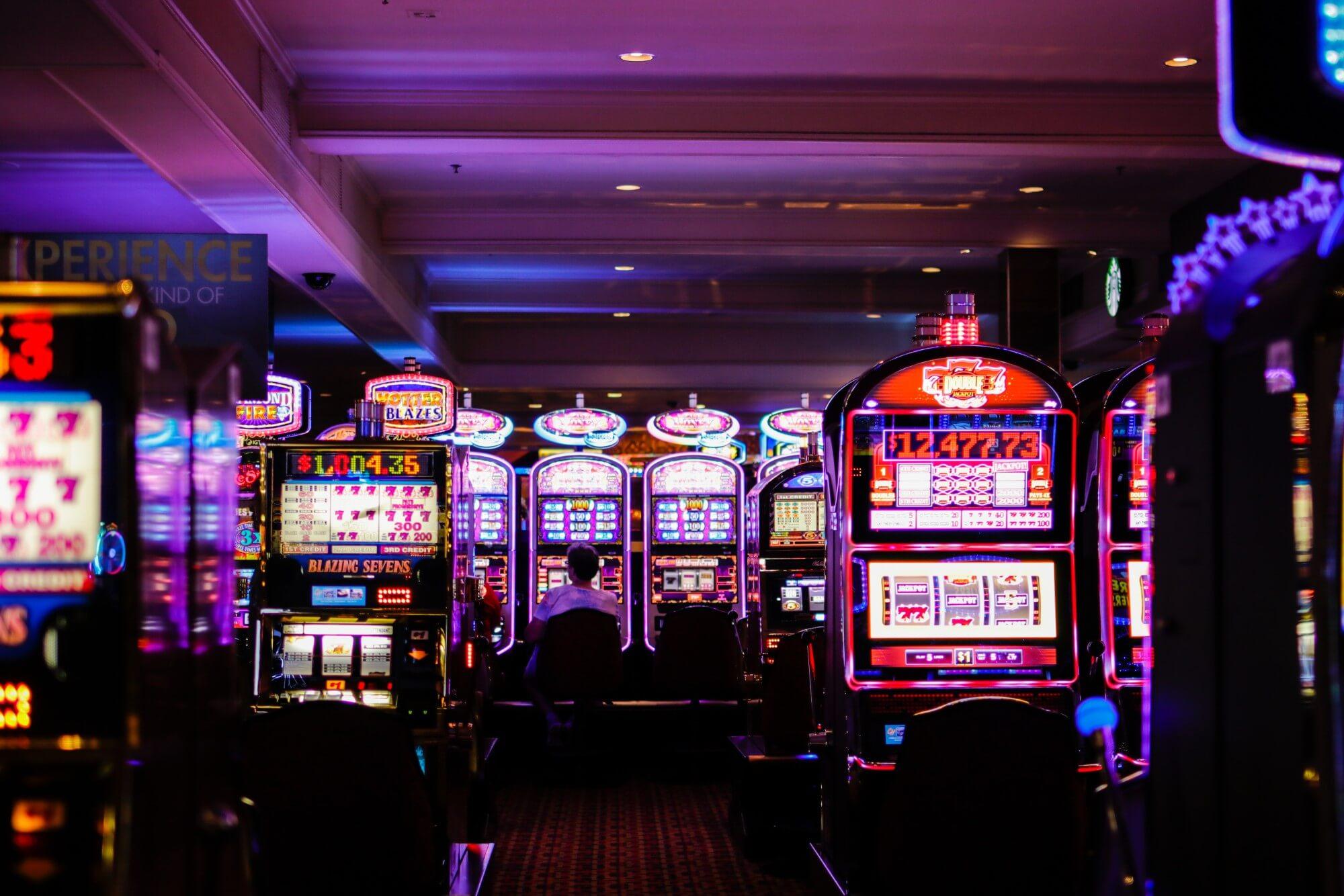 Dimly lit casino floor with slot machines