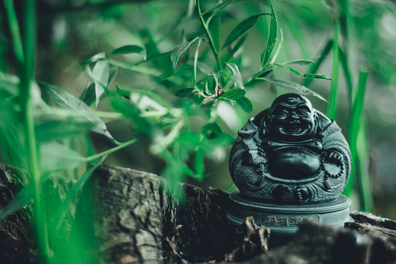 Green laughing Buddha statue, surrounded by green leaves