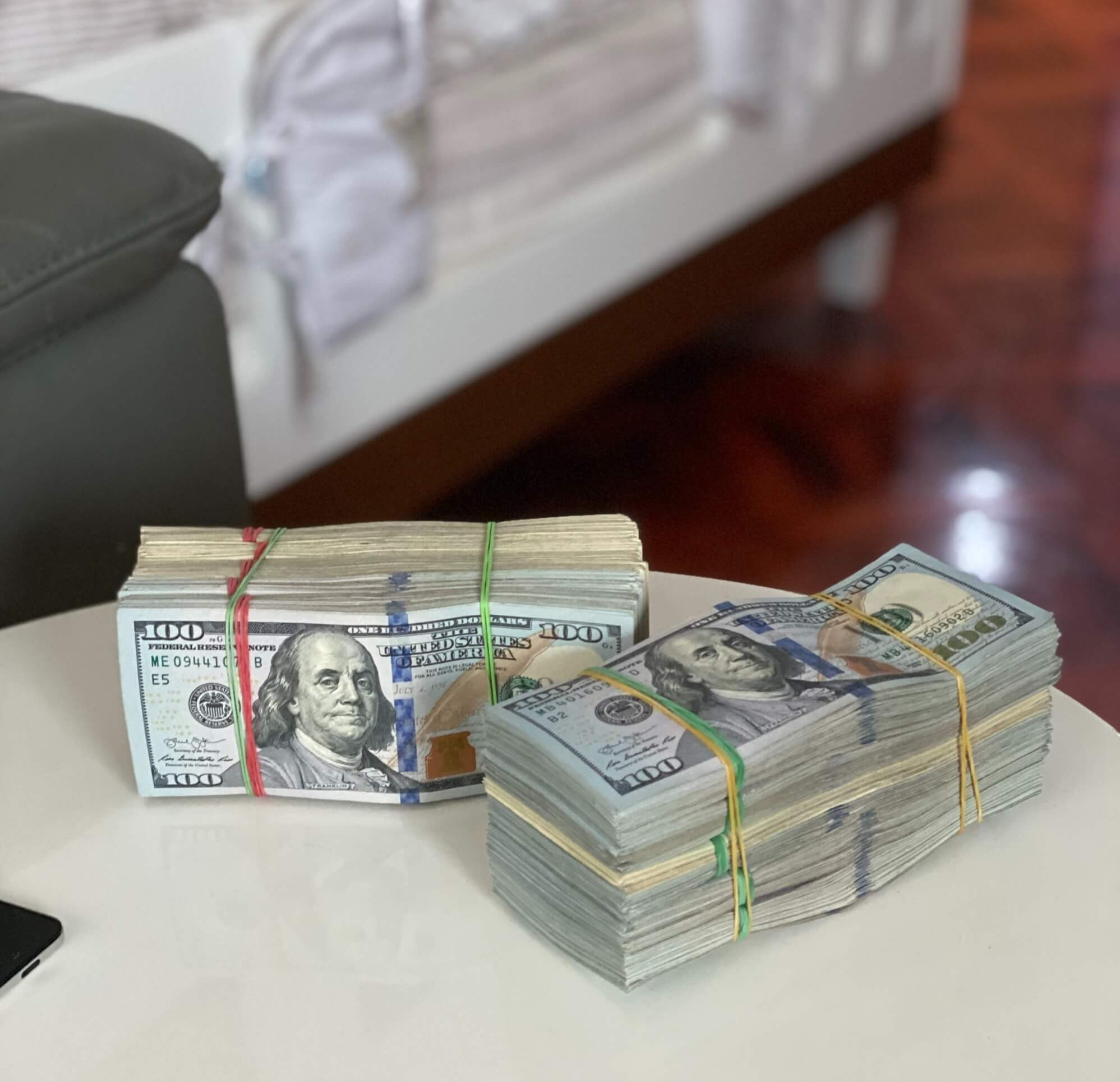 Side table with two, giant stacks of rubber-banded bills.
