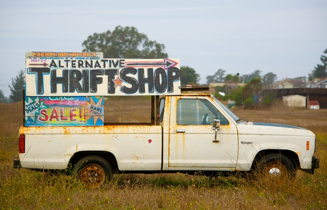 Old truck in a field, large hand painted signs in the bed pointing to a thrift shop and sale