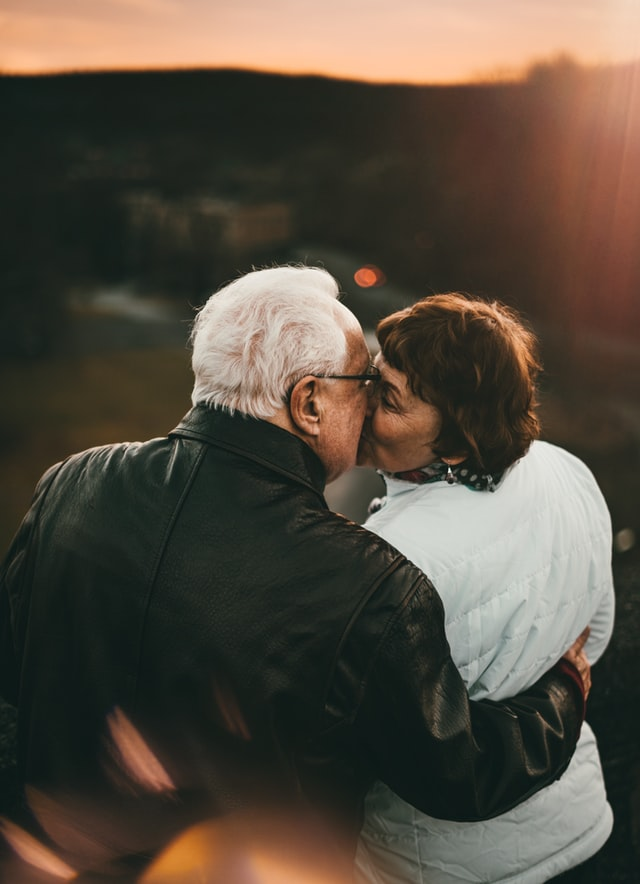 Older couple kissing outdoors
