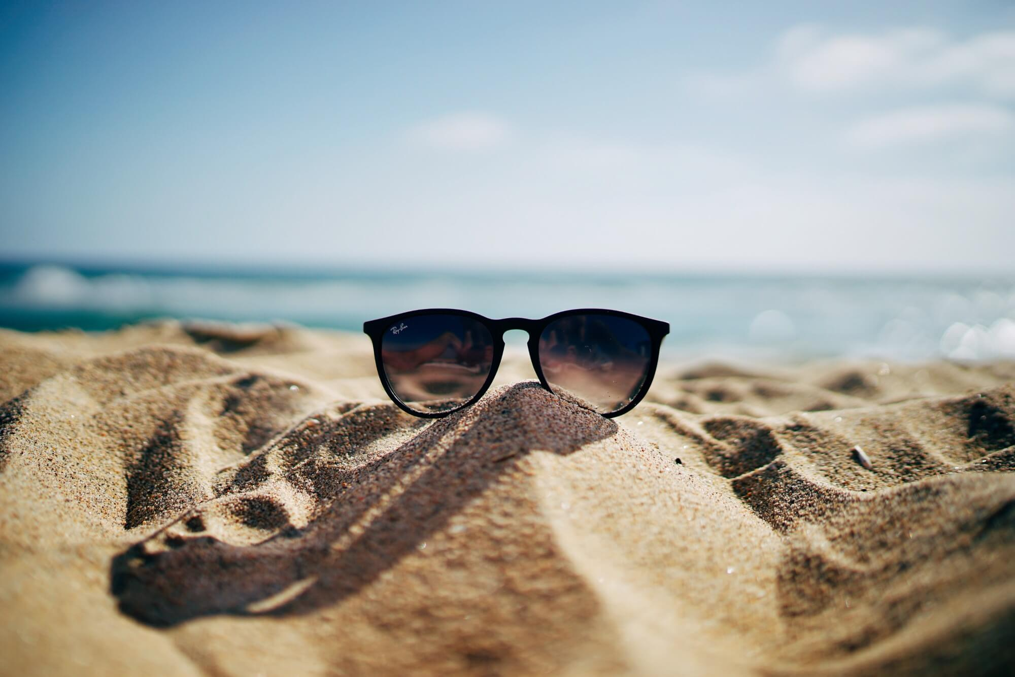 Sunglasses sitting on top of sand pile on the beach
