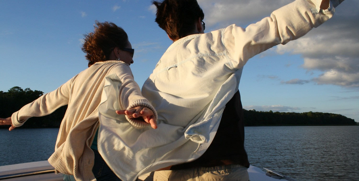 Couple on bow of small boat, doing the Titanic king-of-the-world pose