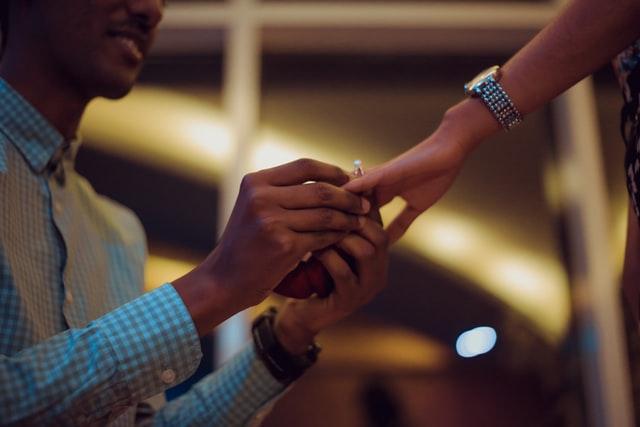 Man placing engagement ring on partner's finger