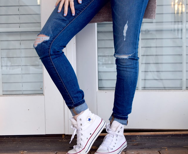 Person standing with jeans on, and bright white shoes