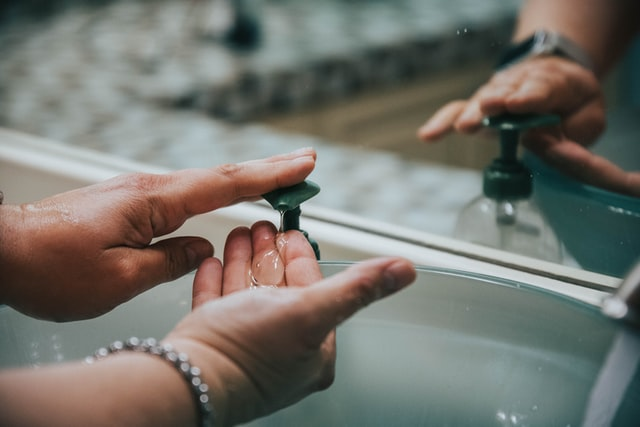 Hands using pump soap at a sink