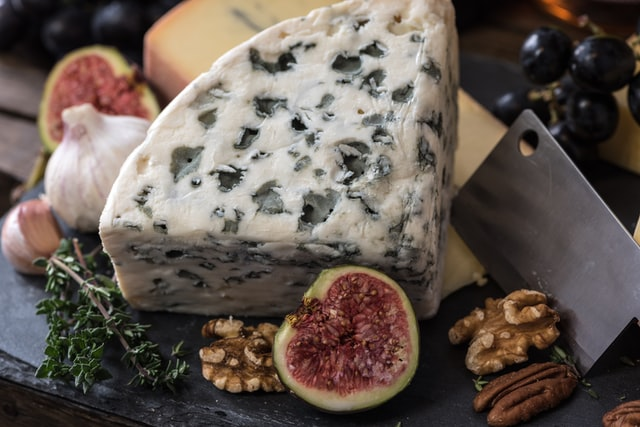Wedge of soft blue cheese, surrounded by figs, nuts, and cheese knife