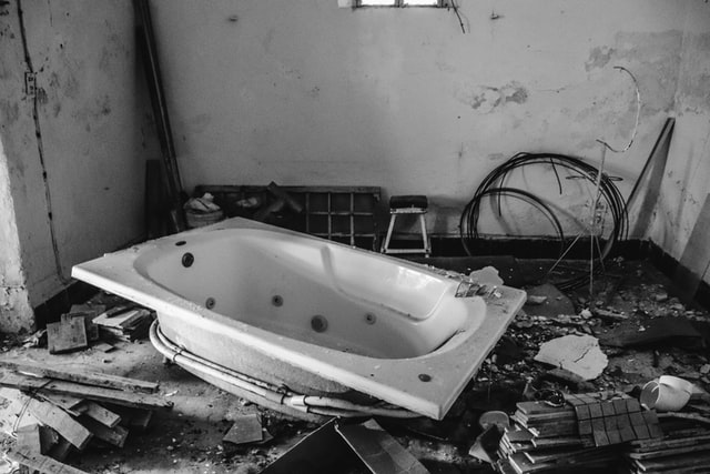 gutted rehab room, with debris everywhere, and bathtub sitting on the floor