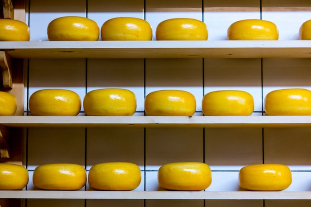Wheels of cheese on aging shelves