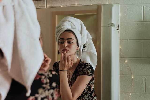 Woman applying makeup in mirror, with towel wrapped around her head