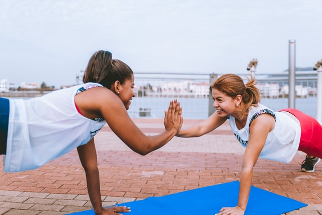 Two women high-fiving while doing planks outside