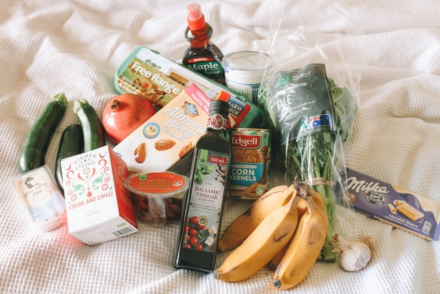 Groceries in a pile on a bed