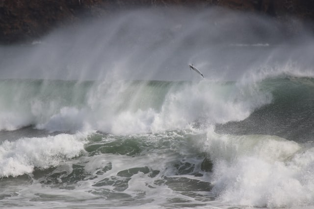 Choppy waves and water spray, with a surf board in the air