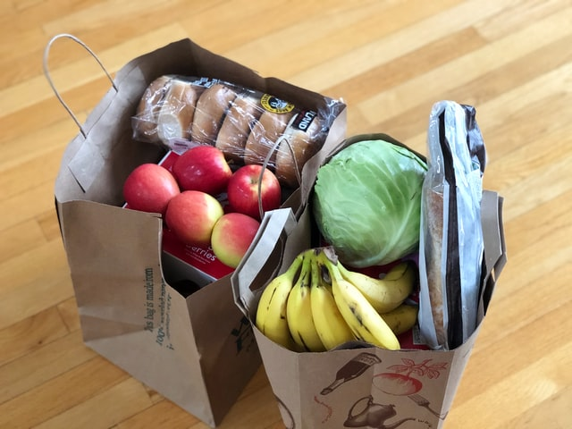 Two grocery bags filled with fruits, veggies, and breads
