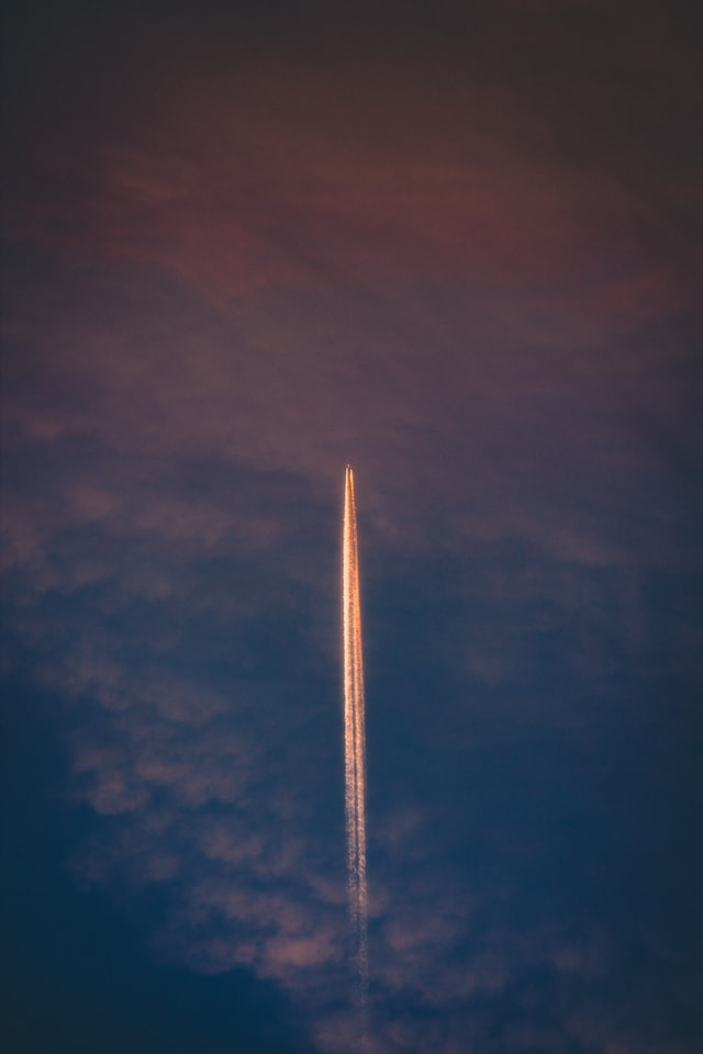 Rocket flying through sky, with trail behind