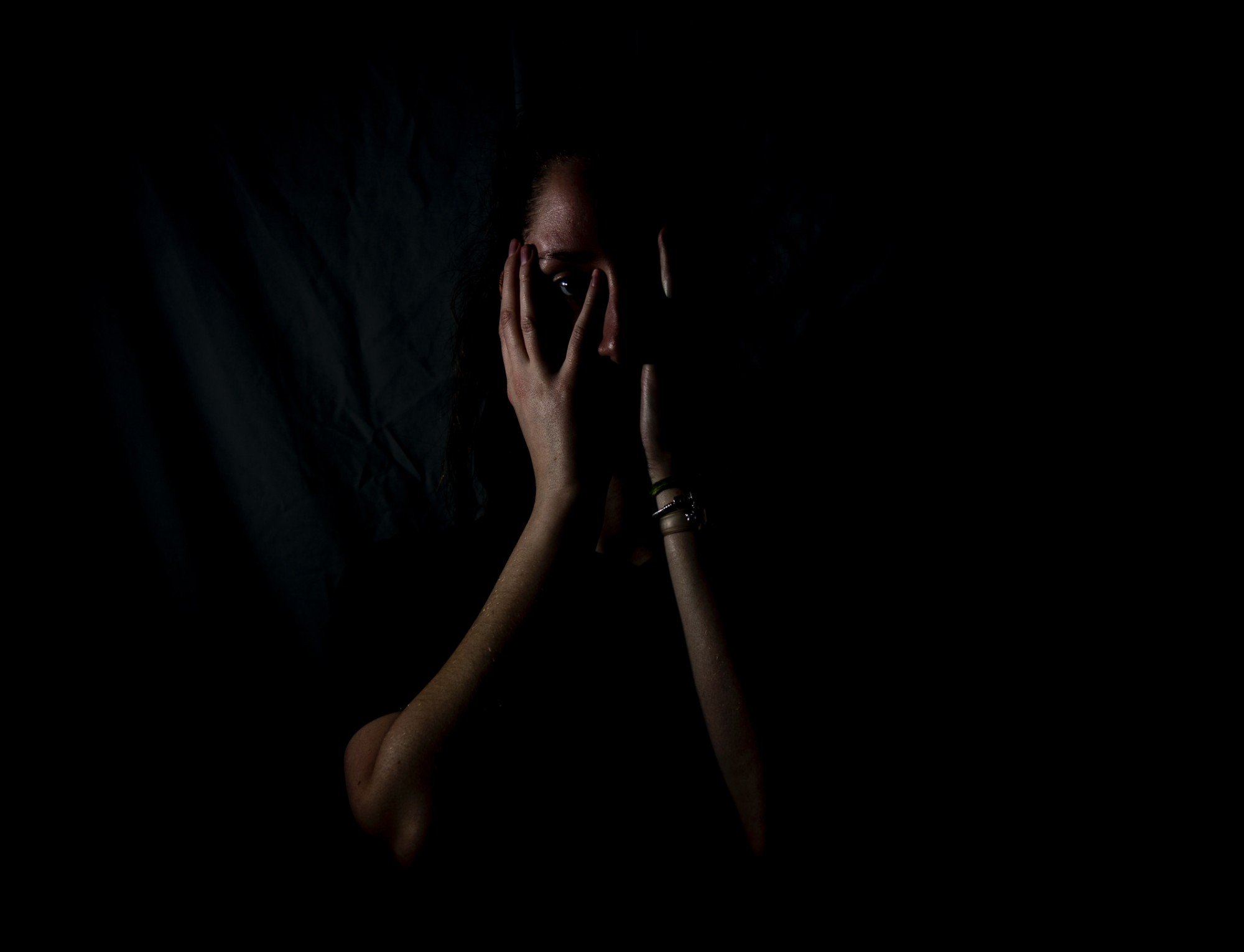 Woman in the shadows, covering her face with her hands