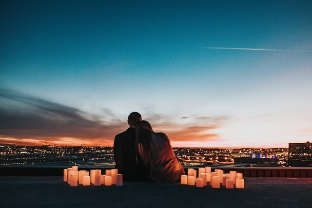 Couple sitting close on roof with candles around them