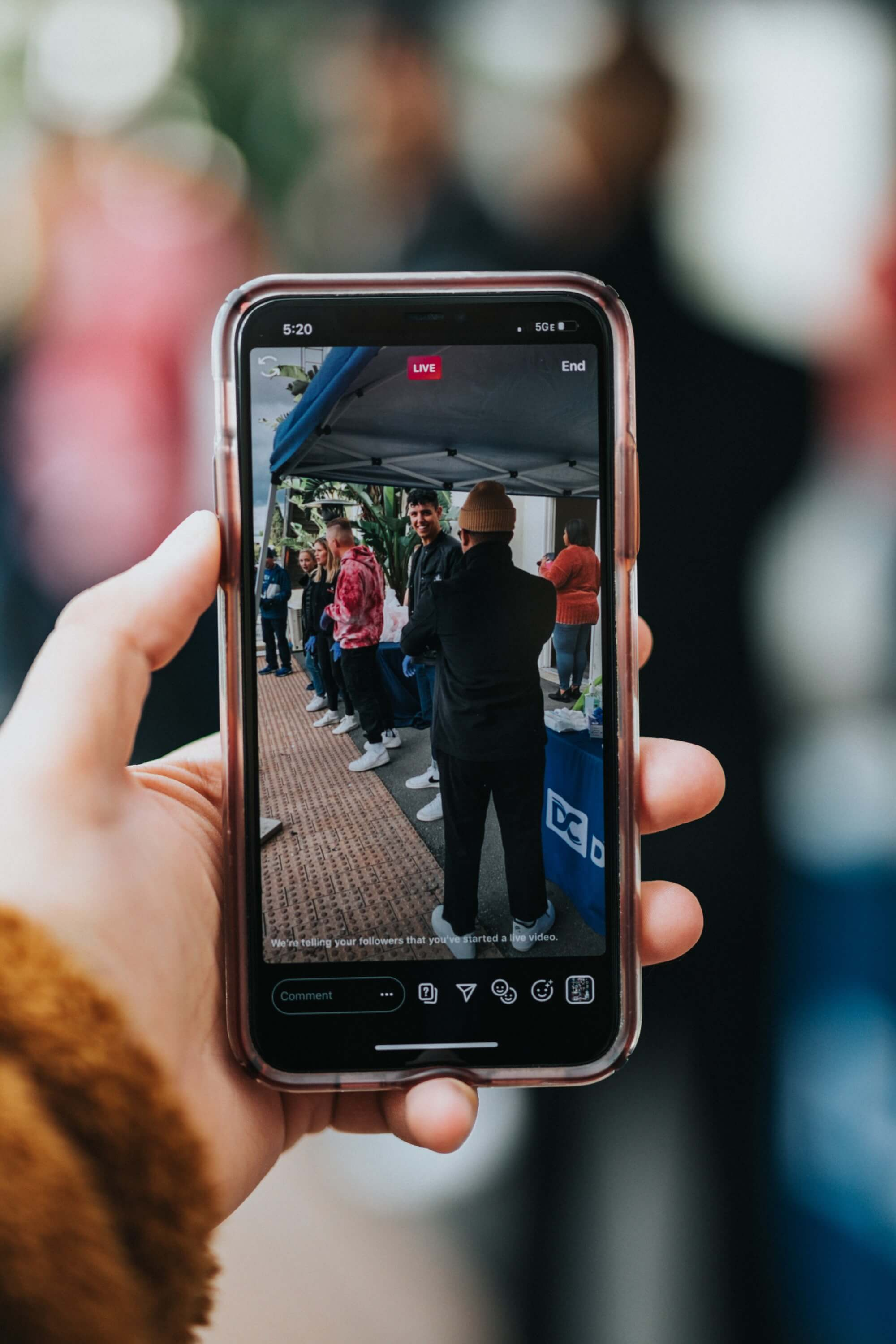 Hand holding iPhone, showing live video on screen