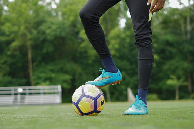 Person standing with foot on soccer ball