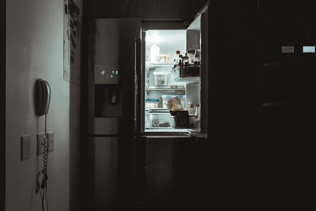 Refrigerator in dark kitchen, with one door open