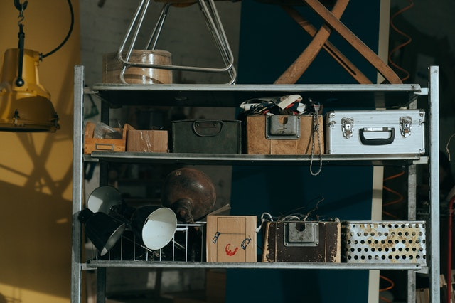 Old metal shelf with vintage boxes and lamps on it