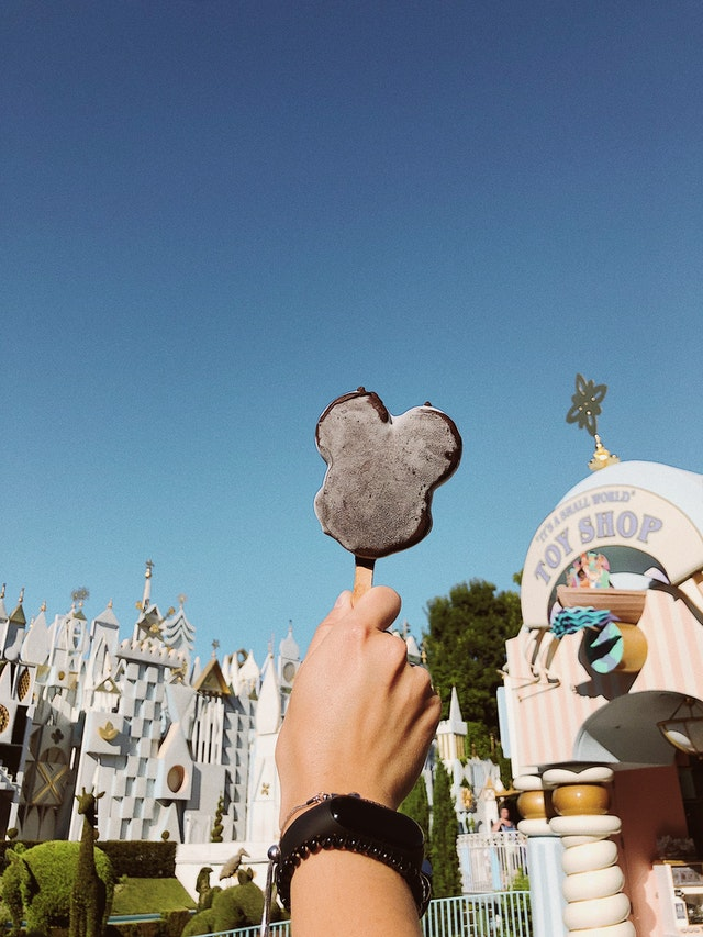 Person holding up mickey mouse popsicle at disneyland