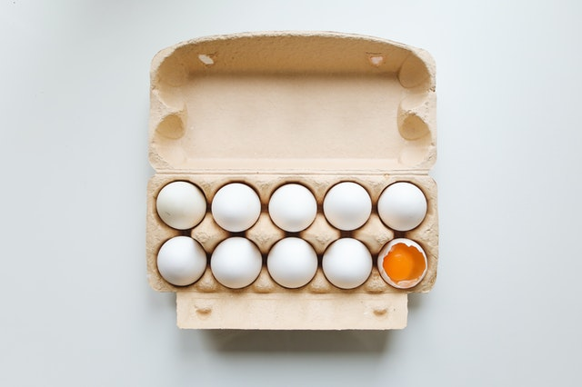 Egg carton, with one egg cracked open