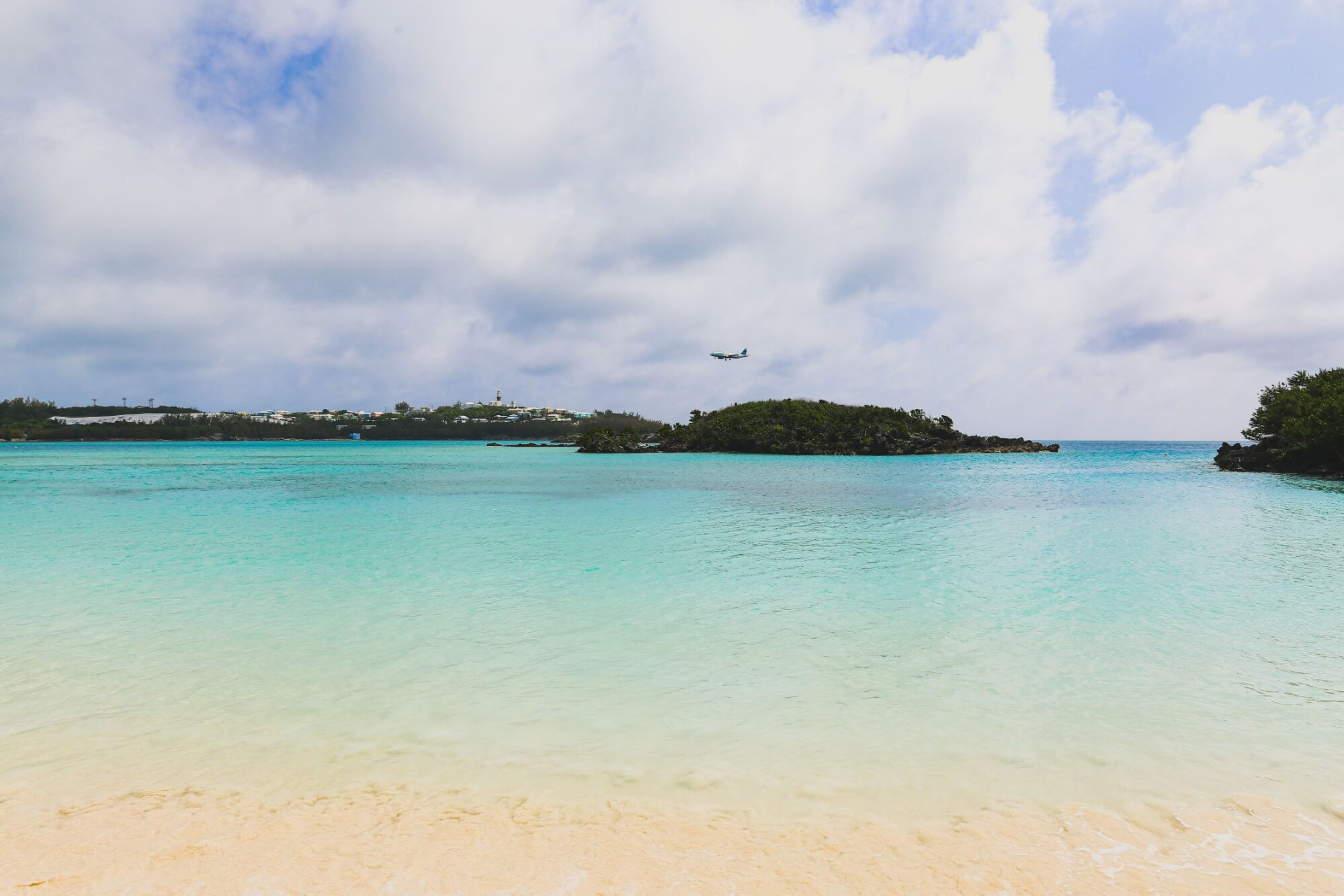 Small plane flying over tropical beach
