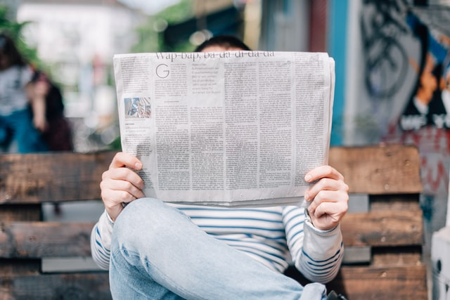 Person on bench holding a newspaper up