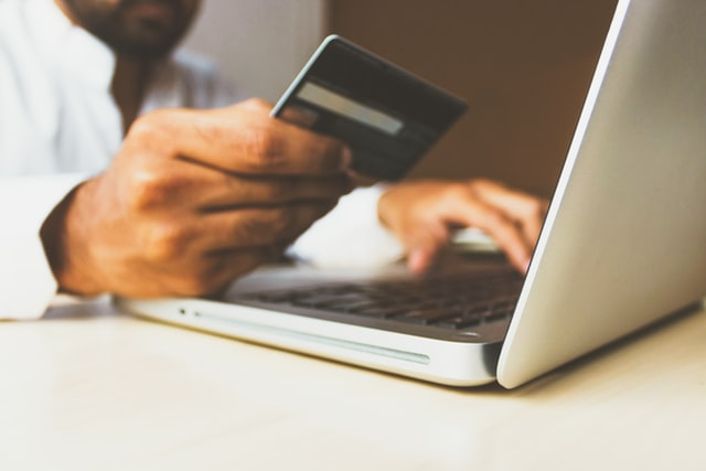 Person holding credit card in hand while using laptop