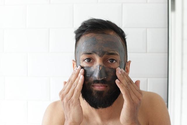 Man applying clay face mask