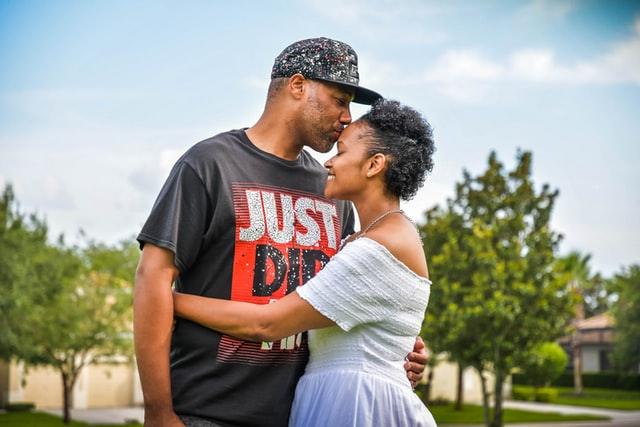 Man kissing woman on her forehead