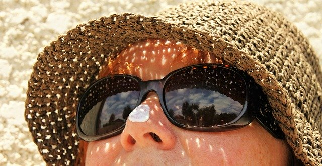 Woman wearing straw hat, with dot of white sunscreen on her nose
