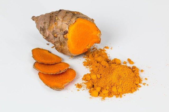 Turmeric root with slices, and small pile of turmeric powder