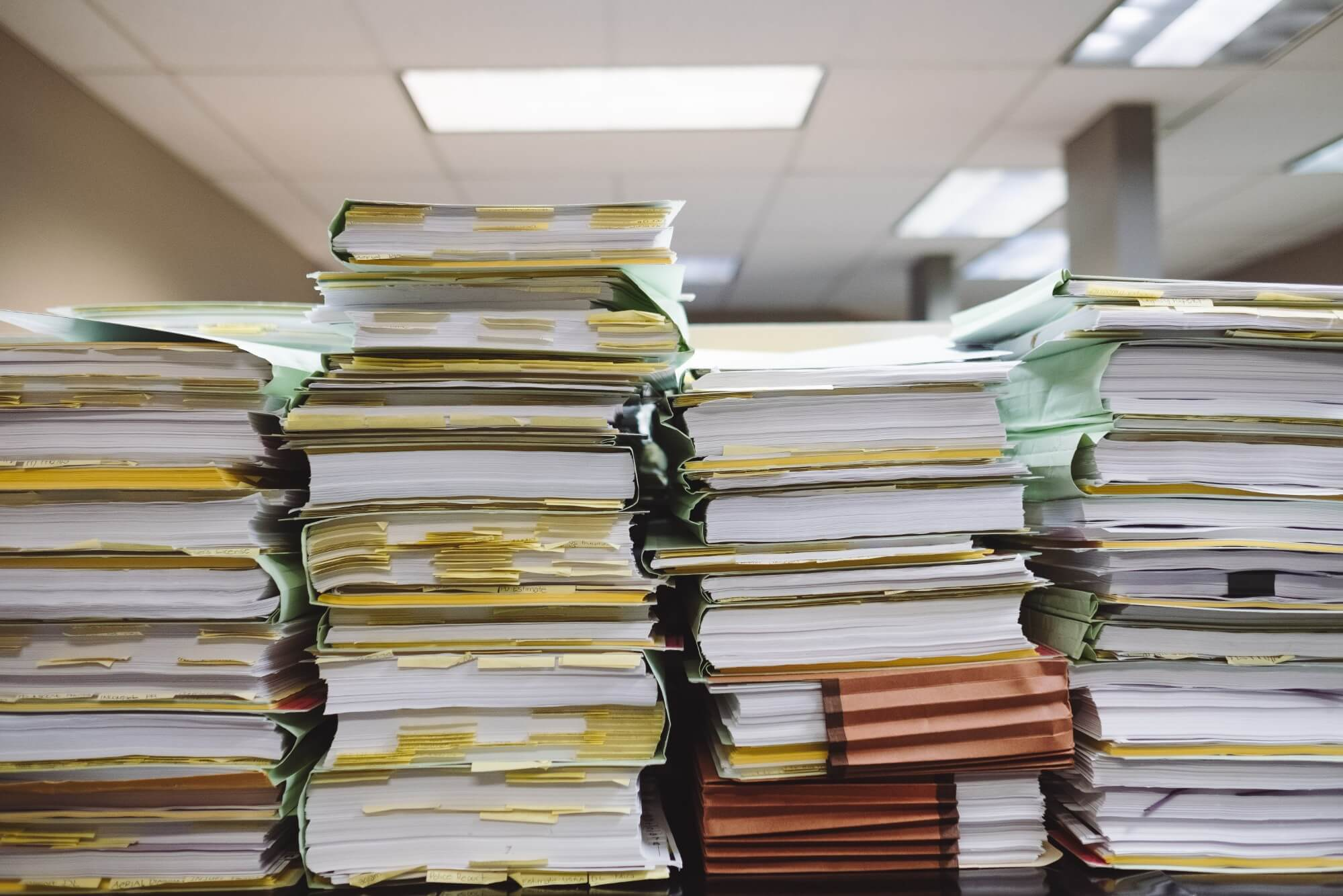 Multiple tall stacks of paperwork