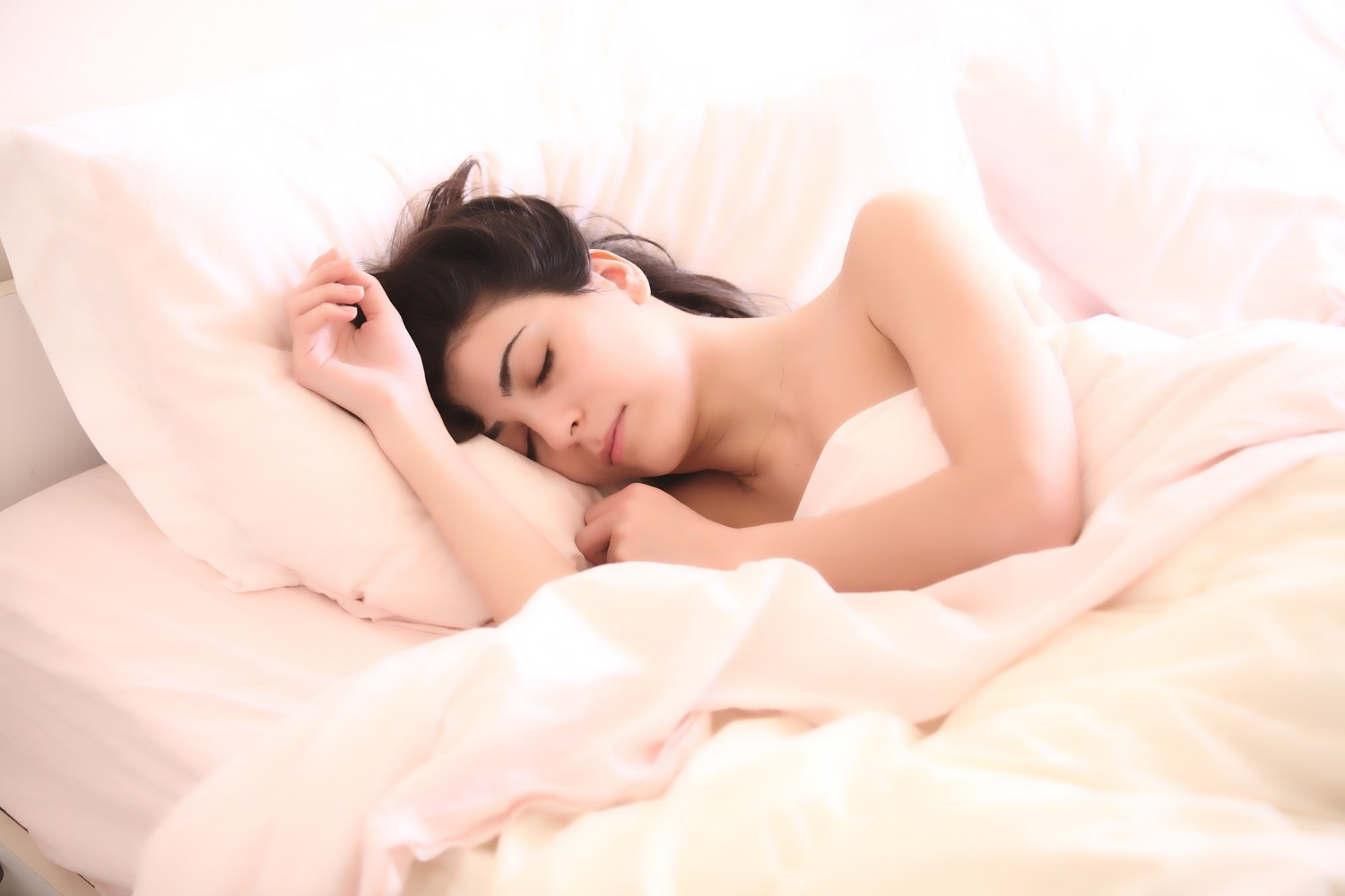Woman sleeping on side in a bed